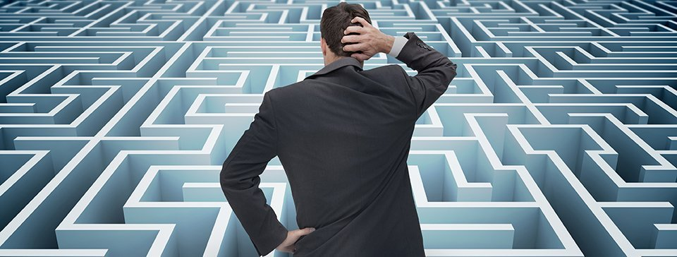 Back of a puzzled businessman getting lost in a huge maze